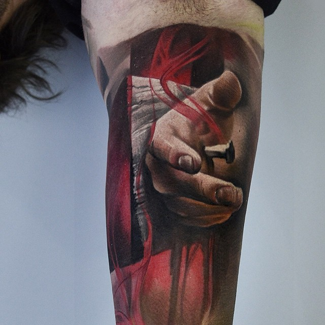 Realism style colored arm tattoo of hand nailed to wooden cross