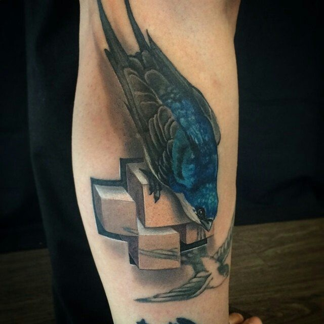 Realism style colored leg tattoo of beautiful bird with stone cross