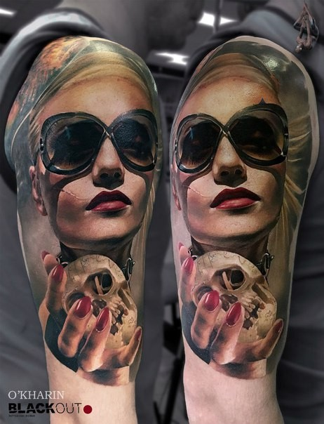 Realism style colored shoulder tattoo of woman with sun glasses and small skull