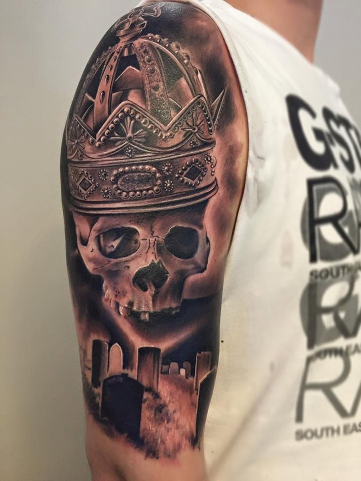 Realism style colored shoulder tattoo of human skull part with big beautiful crown and cemetery