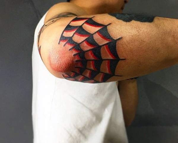 Red and black ink half of spiderweb tattoo on elbow in old school style