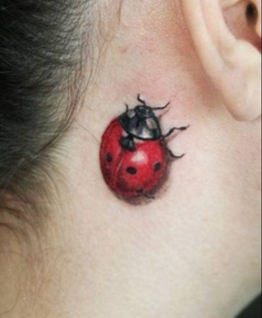 Red ladybug tattoo on neck