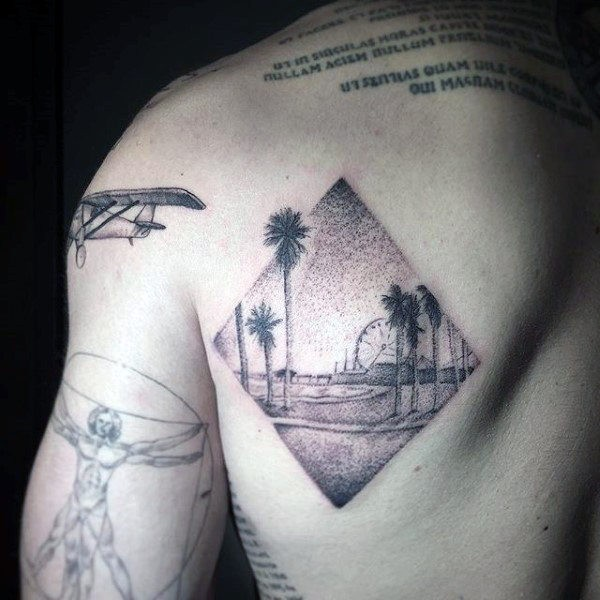 Rhombus shaped dotwork style scapular tattoo of ocean beach with palm trees