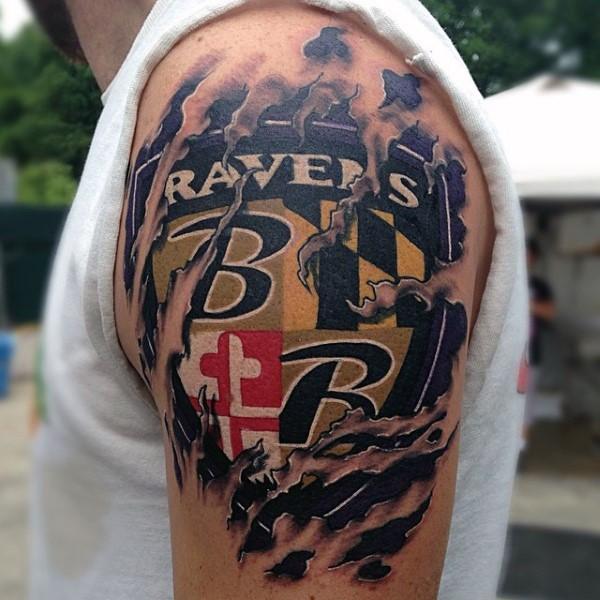 Ripped skin style colored shoulder tattoo of sports team emblem with lettering