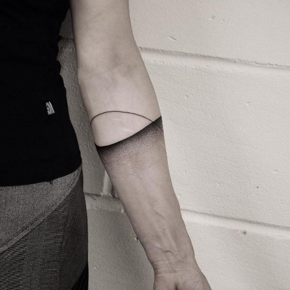 Simple dot style forearm tattoo of sunrise over sea