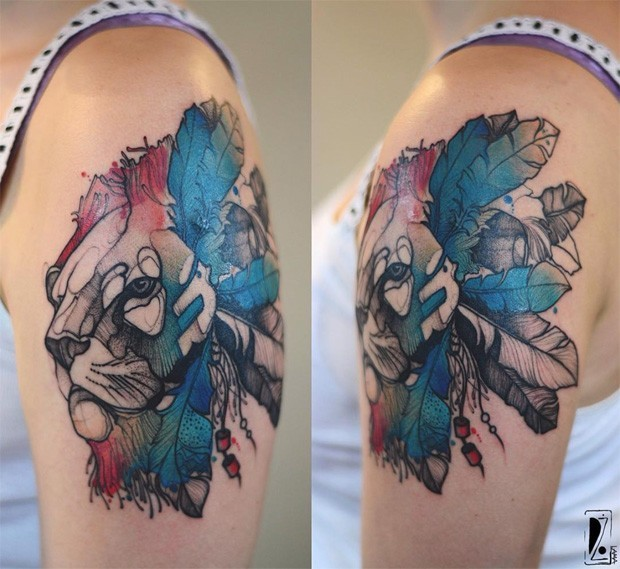 Sketch style colored by Joanna Swirska upper arm tattoo of lion with feather