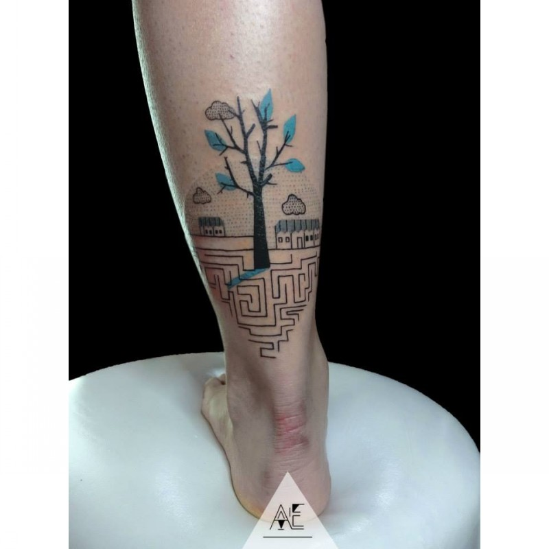 Small beautiful looking ankle tattoo of small tree with labyrinth
