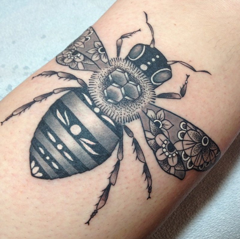 Small black and white bee tattoo stylized with various ornamnets