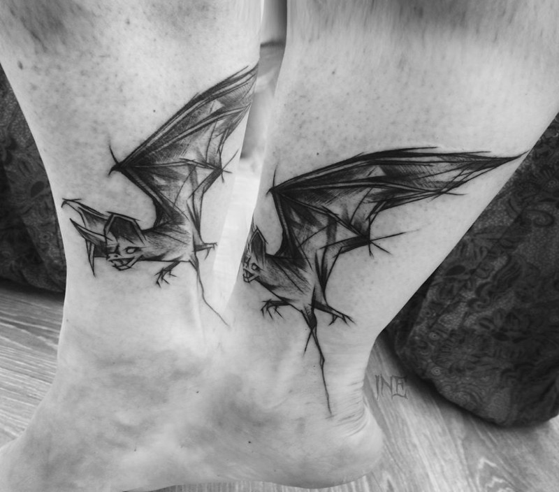 Small black ink ankle tattoo by Inez Janiak of bat