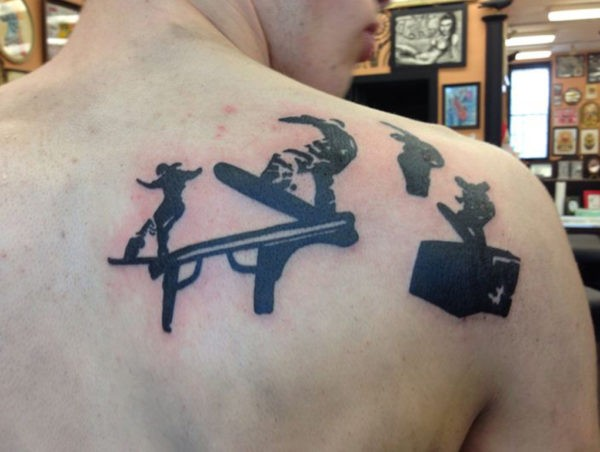 Small black ink scapular tattoo of awesome snowboarder