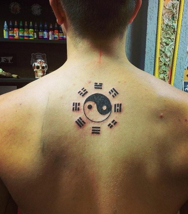 Small black ink Yin Yang symbol tattoo of back