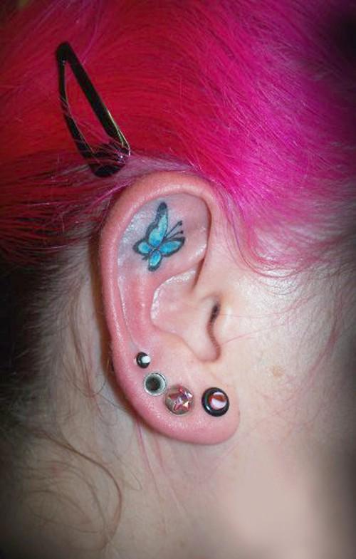 Small blue butterfly tattoo on ear