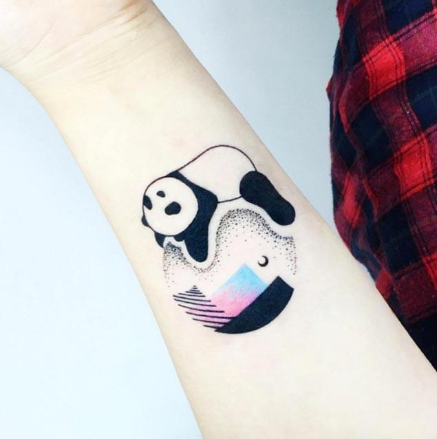 Small cartoon style colored forearm tattoo of sleeping panda on planet