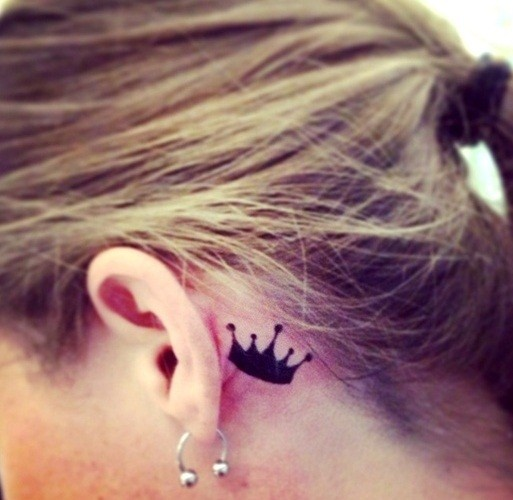 Small crown behind the ear tattoo