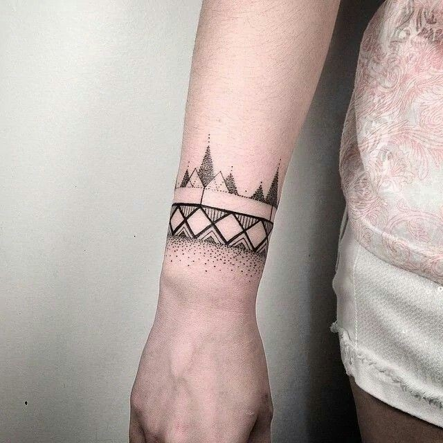 Small dotwork style black ink wrist tattoo of geometrical ornaments