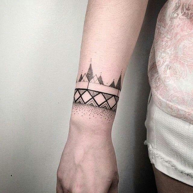 Small dotwork style black ink wrist tattoo of geometrical ornaments