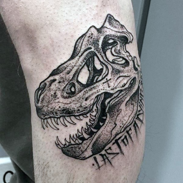 Small engraving style dinosaur skull with lettering tattoo on elbow