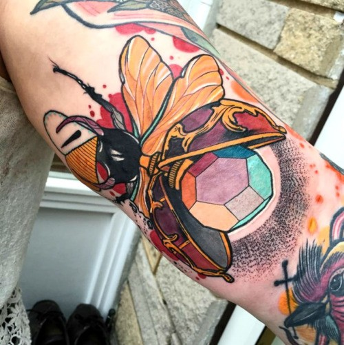 Small illustrative style colored arm tattoo of marvelous bug with stone
