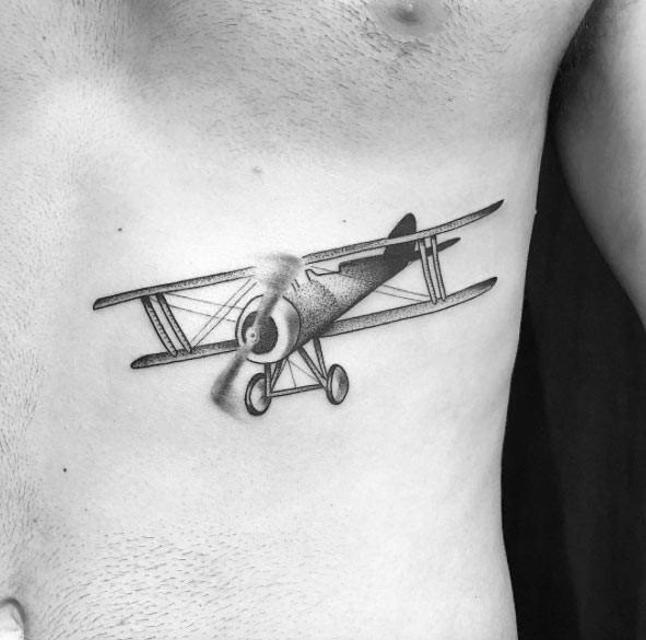 Small stippling style black vintage plane tattoo