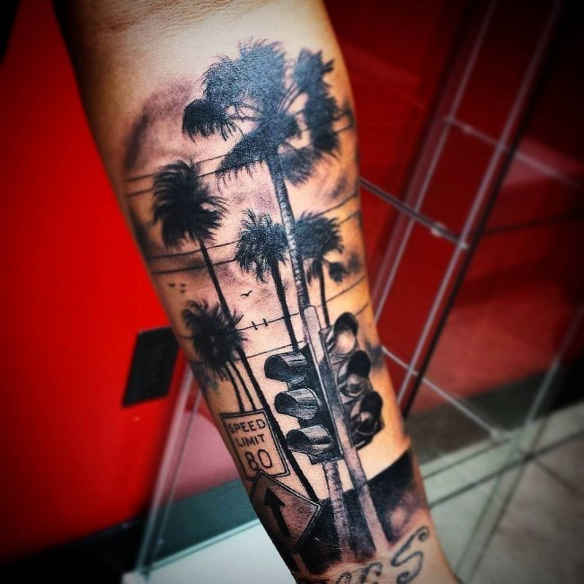 Spectacular looking very detailed arm tattoo of palm tree with road sign
