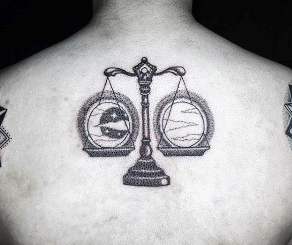 Stippling style black ink upper back tattoo of libra with moon and sun