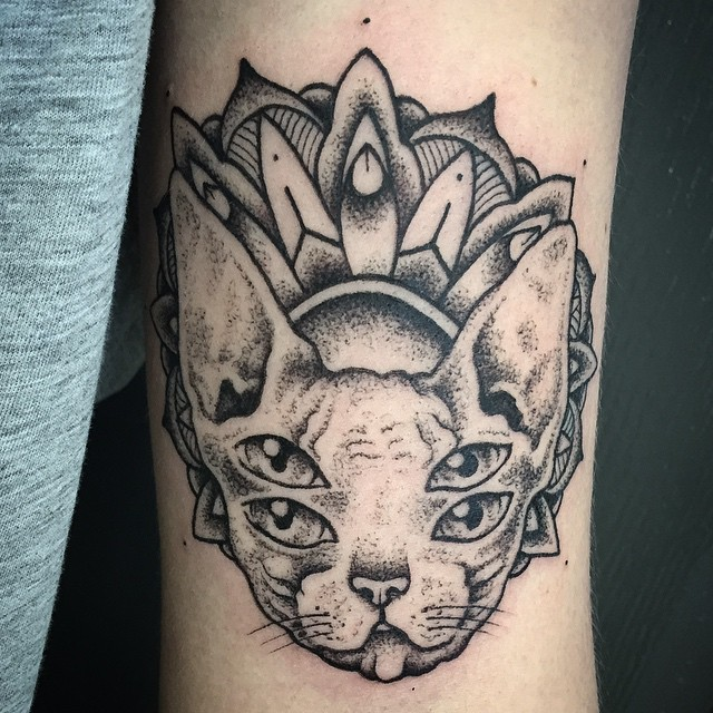 Strange looking blackwork style arm tattoo of sphinx cat head with floral ornament by Michele Zingales