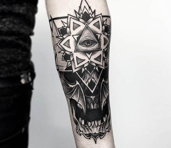Strange looking forearm tattoo of human skull with ornamental flower