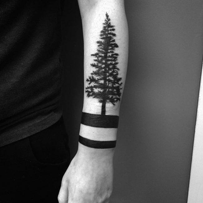 Stunning looking black ink arm tattoo of large tree