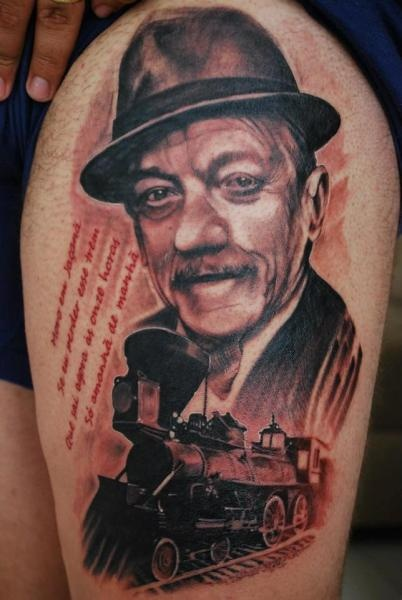 Stunning very beautiful thigh tattoo of train combined with man portrait and lettering