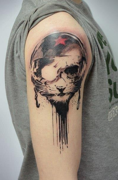 Surrealism style colored shoulder tattoo of cat in bike helmet stylized with red star