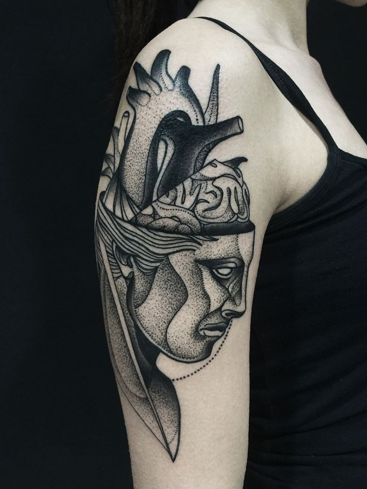 Surrealism style painted by Michele Zingales upper arm tattoo of human head with heart