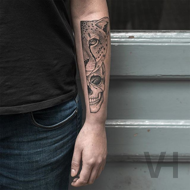 Symmetrical inspired arm tattoo of leopard head with human skull by Valentin Hirsch