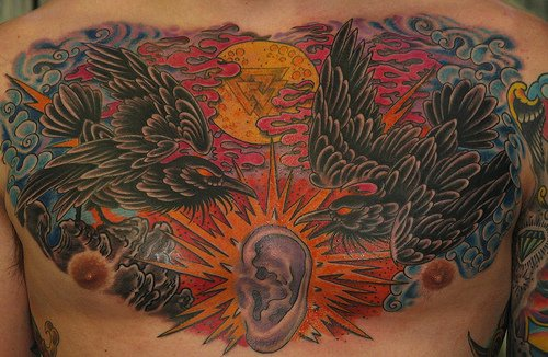 Ear between ravens chest tattoo