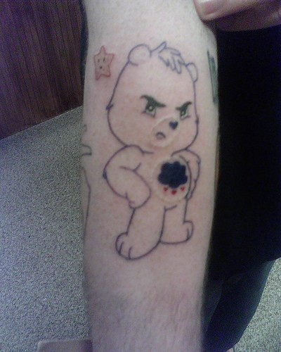 Indignant bear, hearts on the stomach forearm tattoo