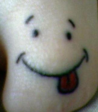 Funny face toe tattoo
