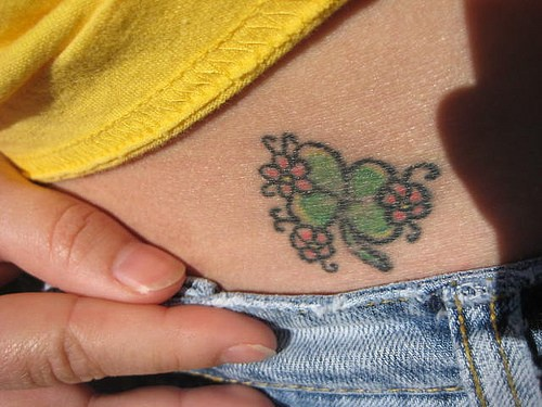 Little, styled with flowers green clover   hip tattoo