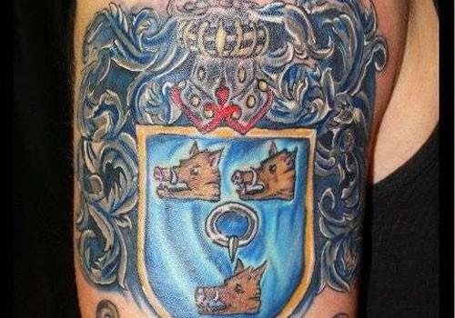 Three boar family crest tattoo on arm