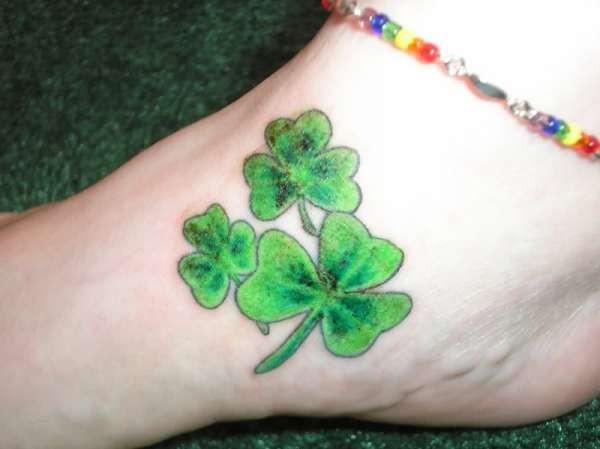Three green irish clover tattoo on foot