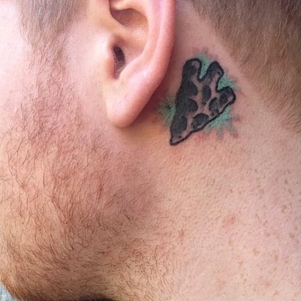 Tiny cartoon like colored behind ear tattoo of antic arrow head