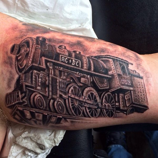 Train tattoo painted in black and gray style on biceps