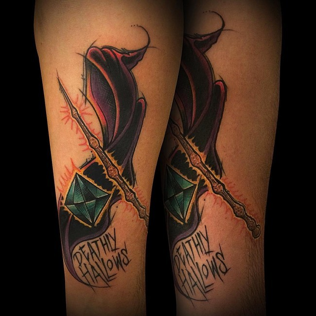 Typical colored arm tattoo of Harry Potter movie magic stick with lettering and diamond