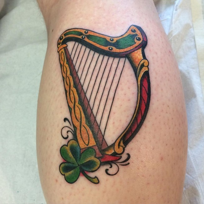 Typical illustrative style colored leg tattoo of harp with clover leaf