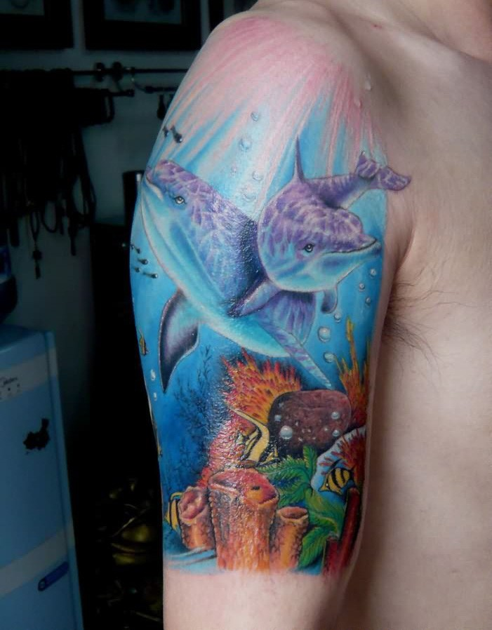 Underwater world and dolphins in ocean tattoo on arm