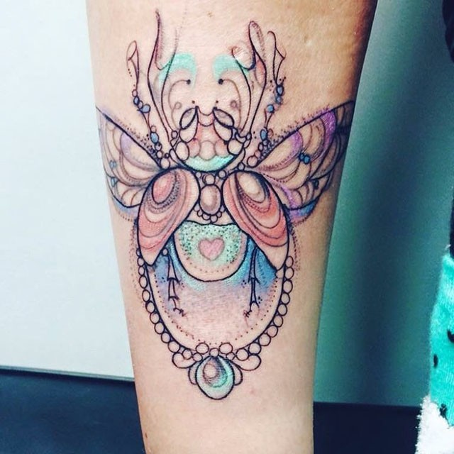 Unfinished stippling style arm tattoo of interesting bug with jewelry