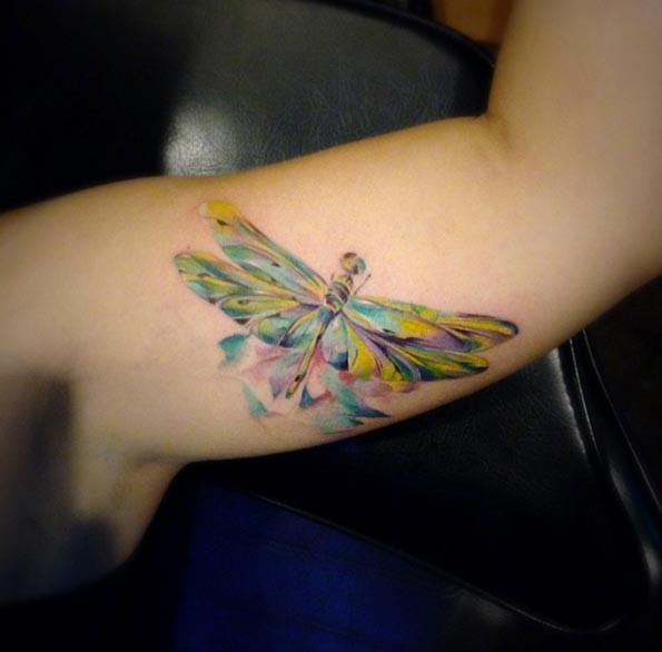 Very beautiful looking colorful dragonfly tattoo on biceps