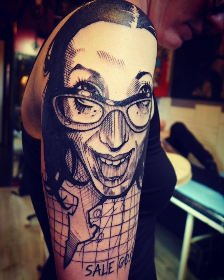 Vintage picture style black ink shoulder tattoo of funny woman with glasses