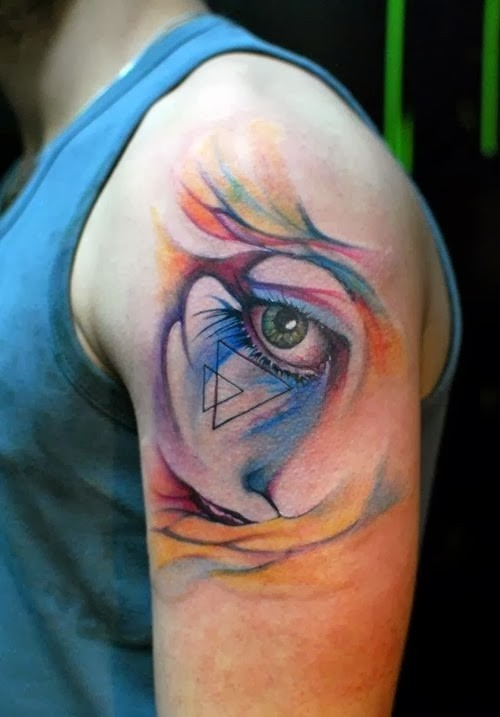 Watercolor style cute looking shoulder tattoo of woman eye stylized with triangles