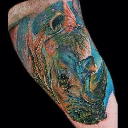 3D like big detailed and colored rhino head tattoo on arm