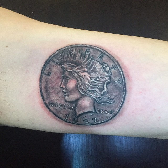 3D like black and white antic coin tattoo on forearm