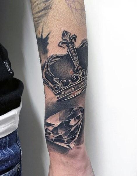 Tatuaje en el antebrazo, corona de rey y diamante